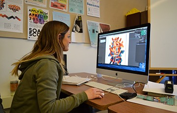 Lauren Wiech works on the design for CREO at a computer in the Mac Lab in Notre Dame Hall.